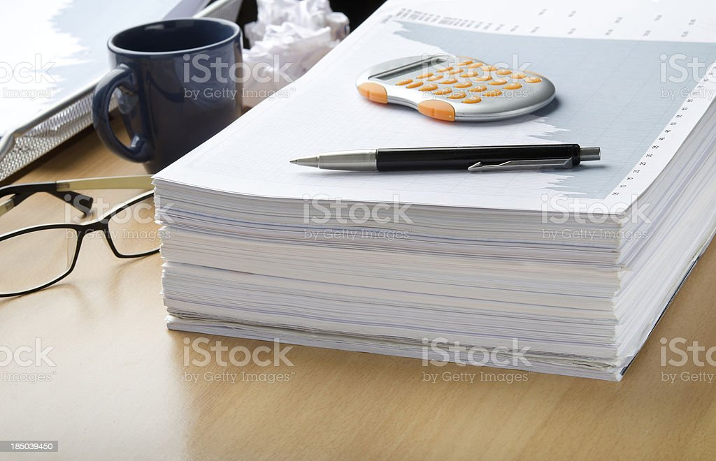 A pile of paperwork with a calculator and pen on top stock photo