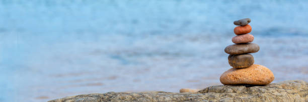 Kieselstapel am Strand, Panorama-blaues Wasser Hintergrund – Foto