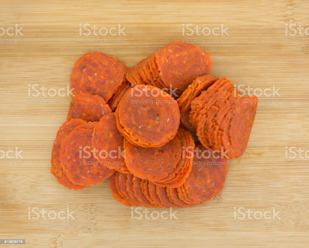Pile of pepperoni slices on a wood cutting board stock photo