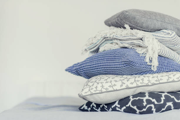 pile of pillows on the edge of the bed, in gray, monochrome pile of pillows on the edge of the bed, in gray, monochrome cushion stock pictures, royalty-free photos & images