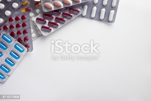 istock Pile of pills in blister packs on a table background 511017606