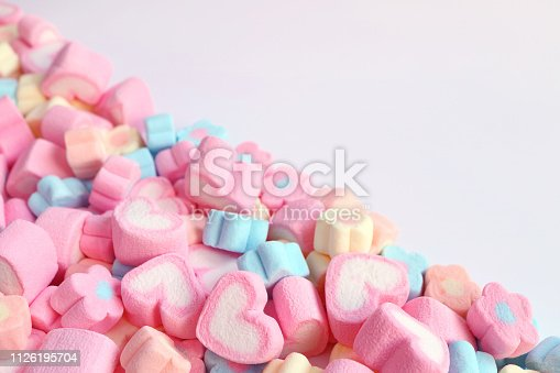 istock Pile of Pink Heart Shaped and Pastel Color Flower Shaped Marshmallow Candies with Free Space for Design or Text 1126195704
