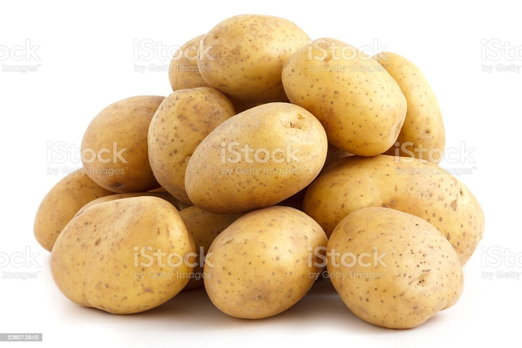 Pile of potatoes arranged on white. stock photo