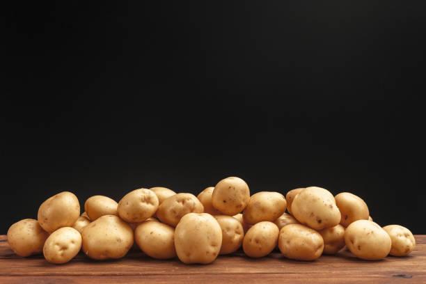 成堆的馬鈴薯躺在木板上 - 薯仔食品 個照片及圖片檔
