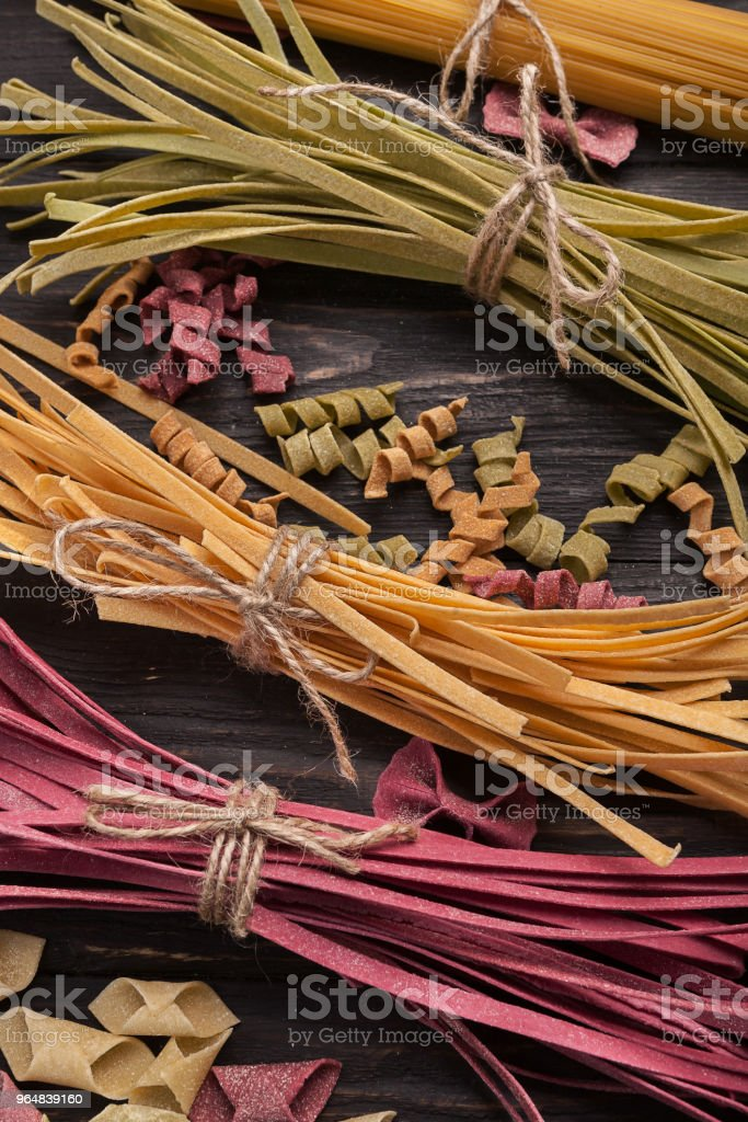 Pile of purple and green fettuccine pasta on wood, closeup royalty-free stock photo