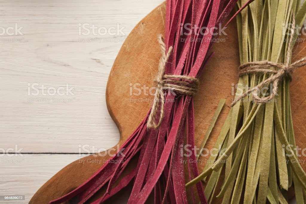 Pile of purple and green fettuccine pasta on wood royalty-free stock photo