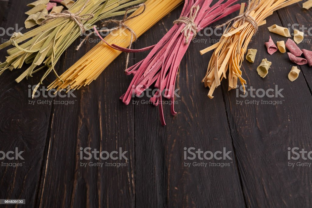 Pile of purple and green fettuccine pasta on wooden background royalty-free stock photo