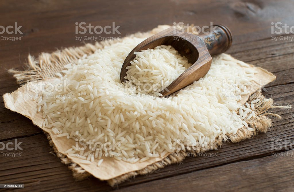 Pile of raw Basmati rice with a spoon stock photo