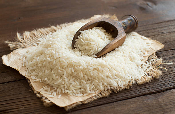 Pile of raw Basmati rice with a spoon Pile of raw Basmati rice with a spoon close up basmati rice stock pictures, royalty-free photos & images