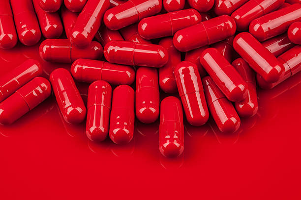 pile of red capsule pills on same color surface - amfetamin pills bildbanksfoton och bilder