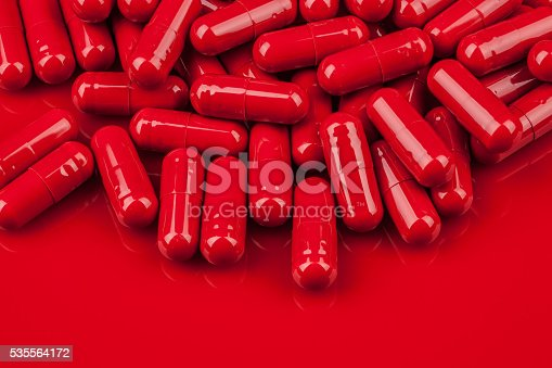 pile of red capsule pills on same color surface stock photo more