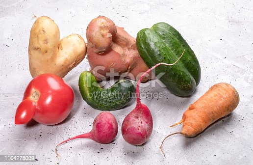 Pile of ripe ugly vegetables: potatoes, tomato, cucumbers, carrot and radishes on concrete background. Waste zero concept.