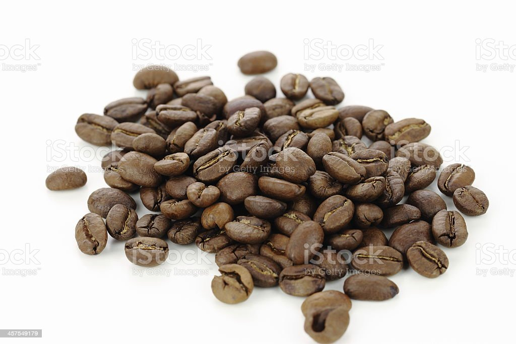 Pile of roasted whole coffee beans on a white background stock photo