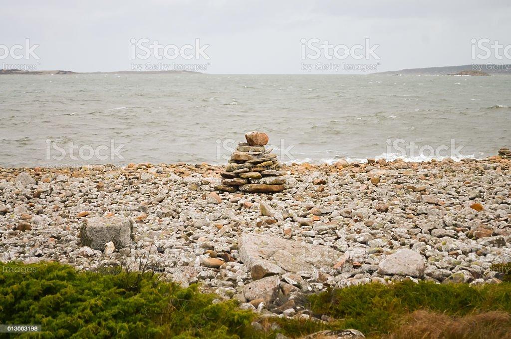 pile of rocks at a windy and rainy coast stock photo