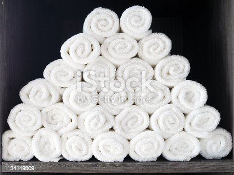 Pile of rolled white clean towel placed on the closet in the gym, ready to use for the work out person. Selective focus.