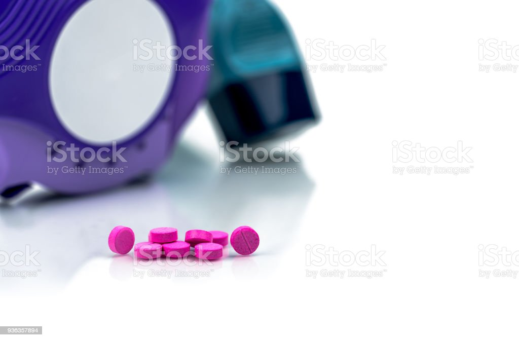 Pile of round pink small tablets pills on blurred background of asthma inhaler an accuhaler. Bronchodilator medicine for treatment asthma in adult. Salbutamol (Albuterol) tablets pills. stock photo