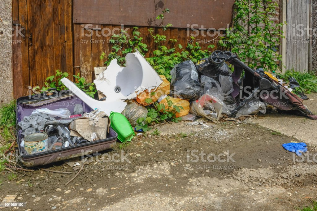 Pile of rubbish, rotting after being fly tipped and left in an urban alleyway.  Demonstrates anti-social behaviour. stock photo