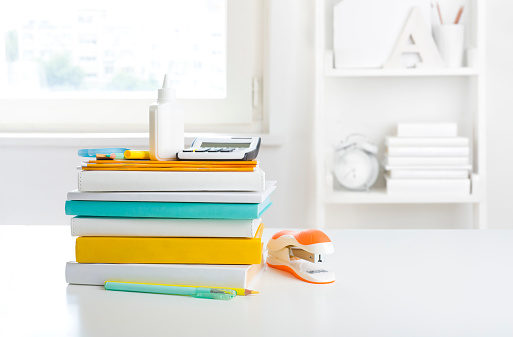 Pile of school books and supplies on white bookshelf background