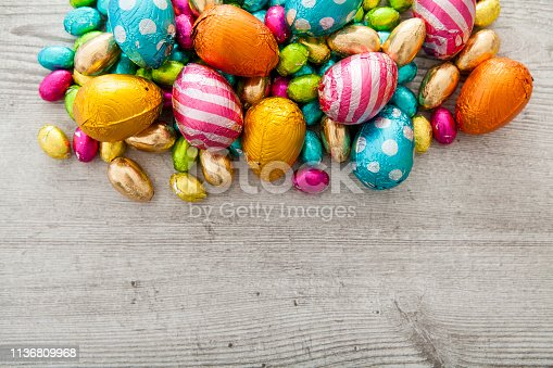 Mini chocolate Easter eggs on grey wood as a border with copy space