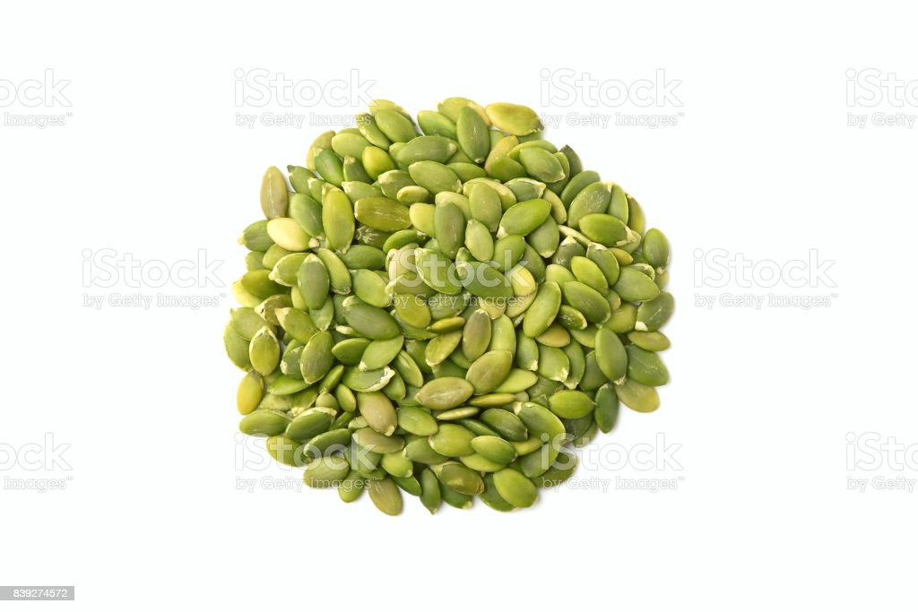 Pile of shelled pumpkin seeds on white background stock photo