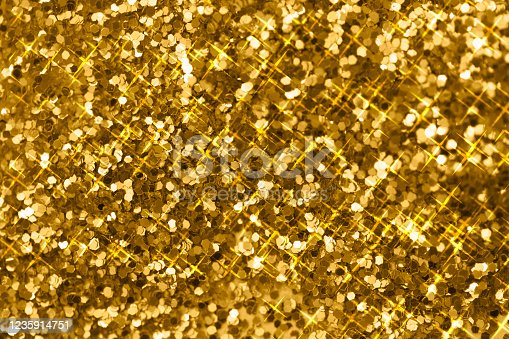 Pile of shining gold pieces seen from above. Top view macro image of sparkling gold dust for backgrounds and textures