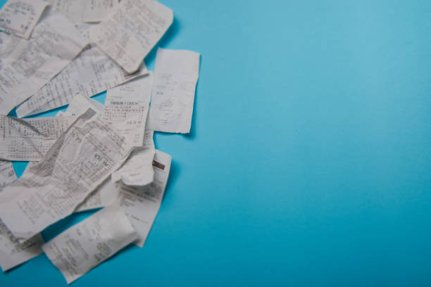 pile of shopping receipts on blue background - receipt stock photos and pictures