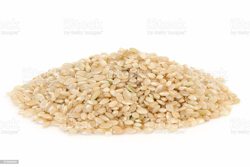 Pile of short grain brown rice on white royalty-free stock photo