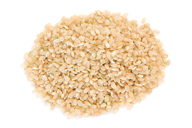 Pile of short grain brown rice on white stock photo