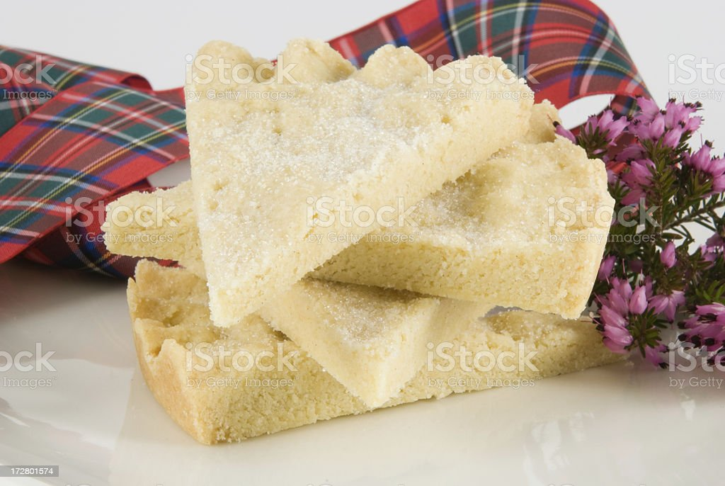 pile of shortbread with red tartan ribbon and heather stock photo
