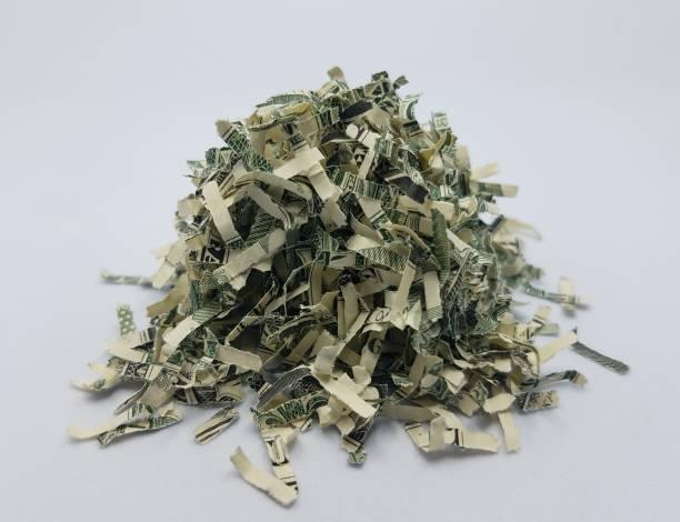pile of shredded United States money on white background stock photo