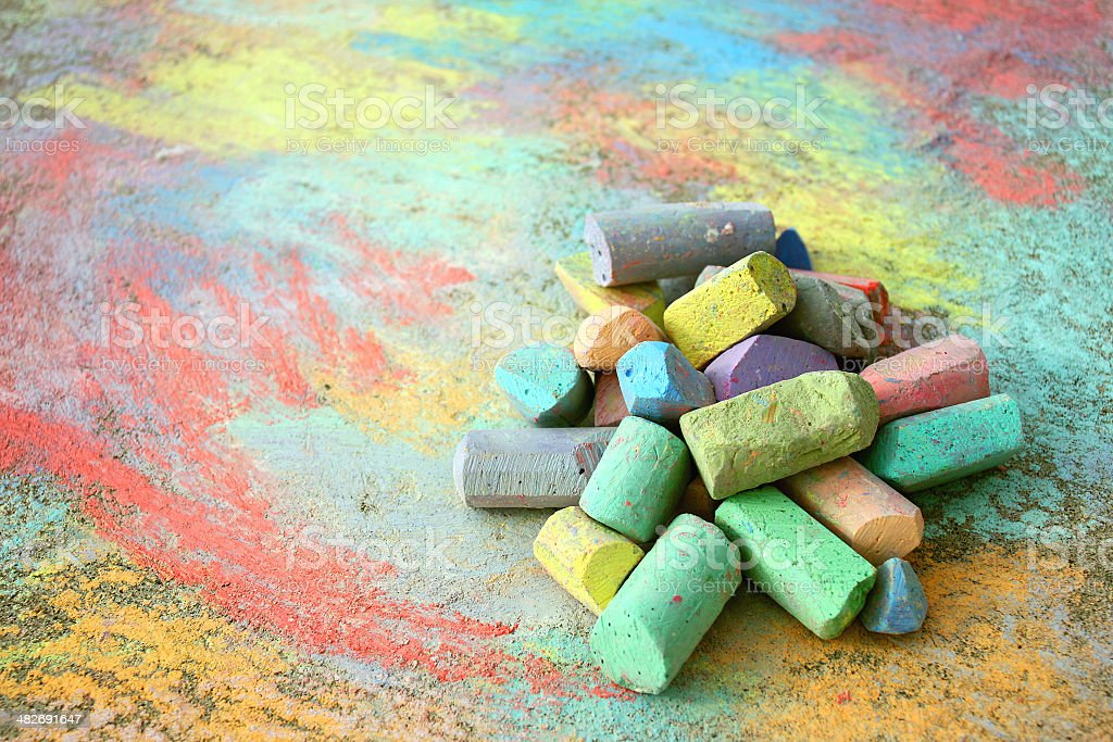 Pile of Sidewalk Chalk a collection of colorful sidewalk chalk is piled up on a rainbow drawing, outside on the pavement. Art Stock Photo