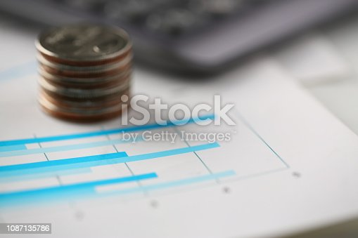 istock Pile of silver coins stand at financial graph papers 1087135786