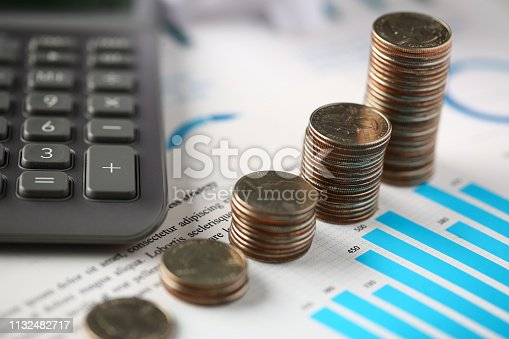 istock Pile of silver coins stand at financial graph papers 1132482717