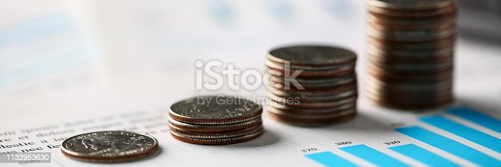 istock Pile of silver coins stand at financial graph papers 1133953630