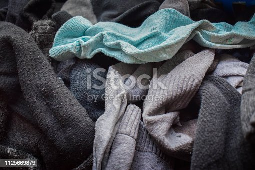 A heap of mismatched socks in different colors and textiles.