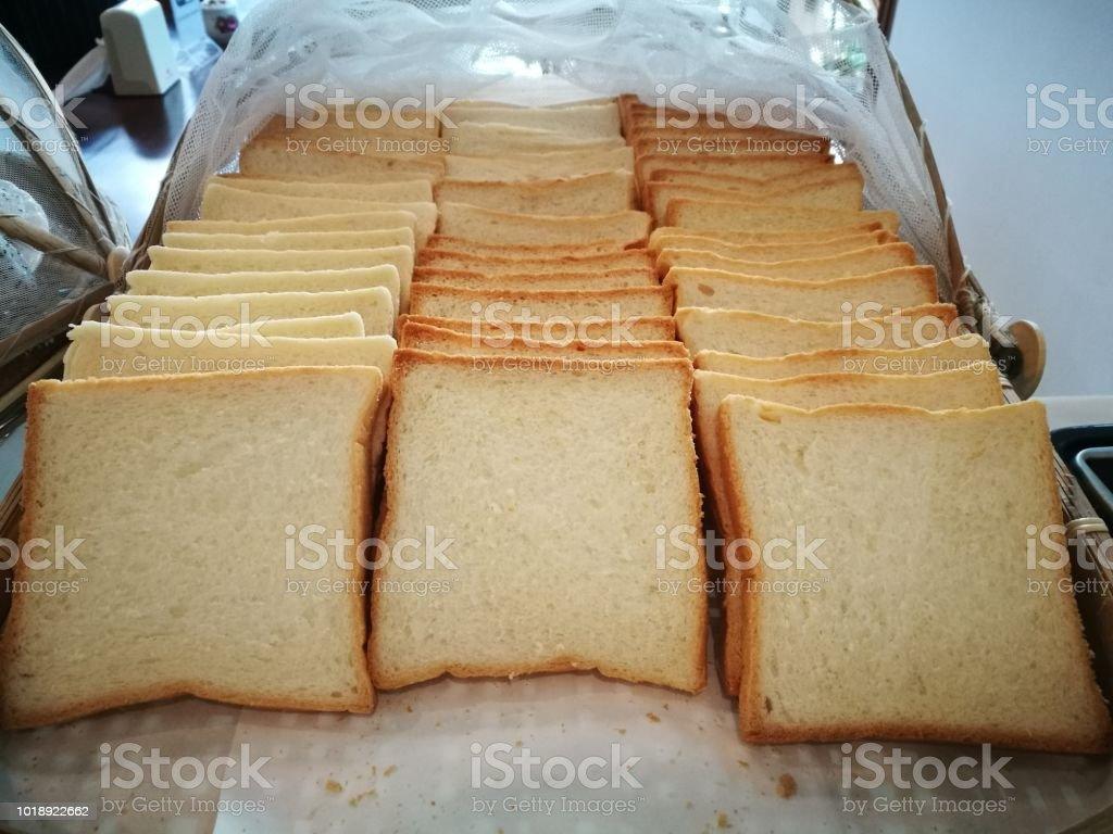Pilha de fatia fresco perfumado pão na chapa branca em utensílios de cozinha, colocar na mesa de madeira. - foto de acervo