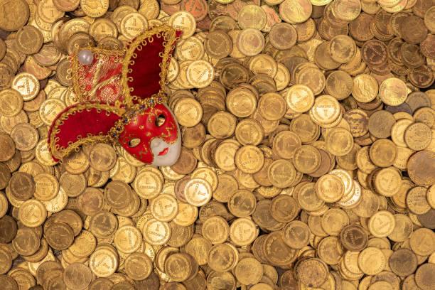 Haufen von kleinen goldenen Münzen mit venezianischer Maske – Foto