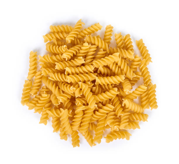 pile of spiral pasta isolated on white background pile of spiral pasta isolated on white background fusilli stock pictures, royalty-free photos & images