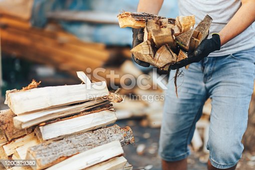 A pile of stacked firewood, prepared for heating the house. Gathering fire wood for winter or bonfire. Man holds fire wood in hands.
