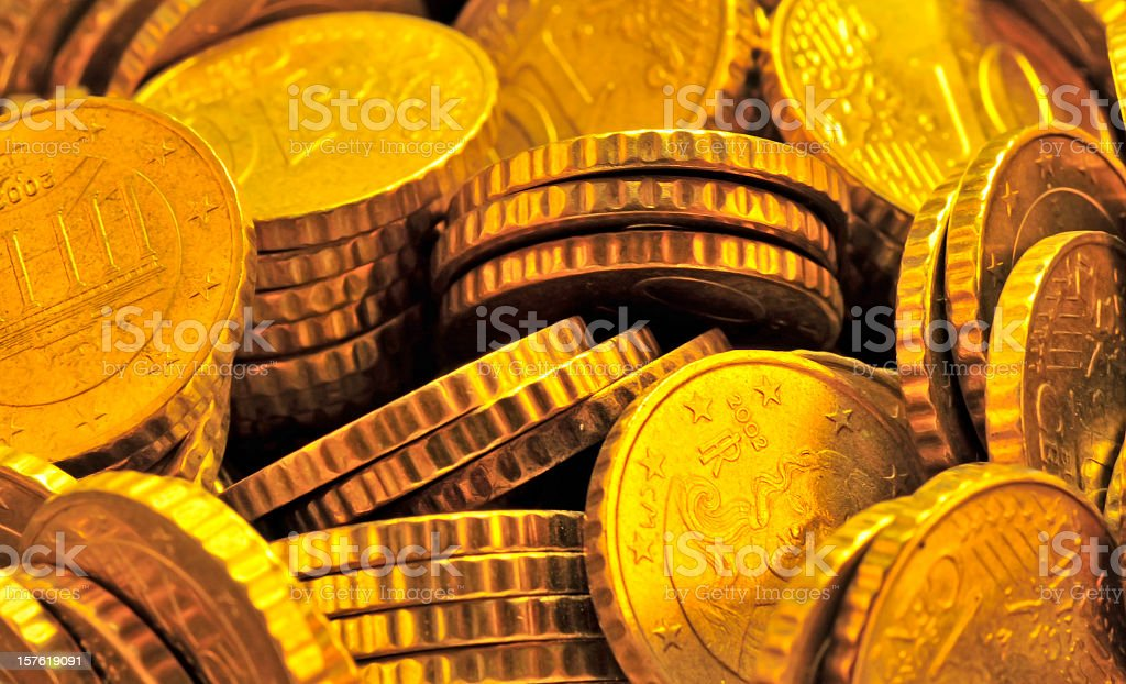 Pile of stacked shiny golden coins close-up full frame royalty-free stock photo