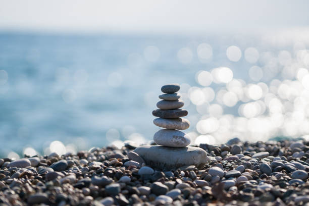 pile of stones at the beach - stack rock stock pictures, royalty-free photos & images