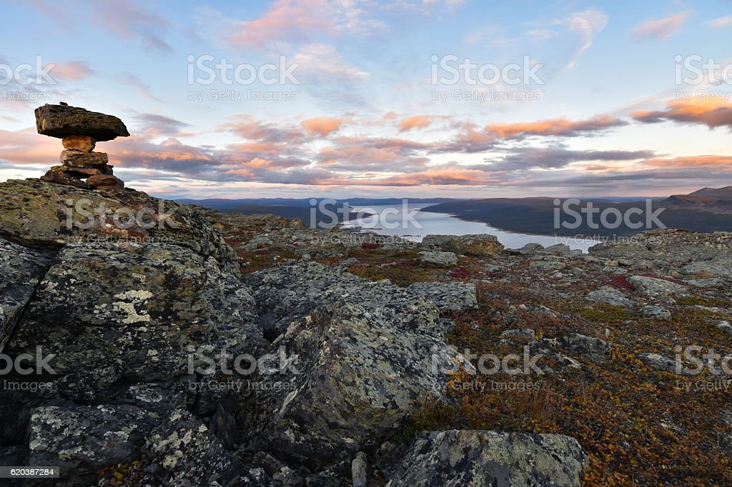Pile of stones marks mountain top, sunset and lake background foto