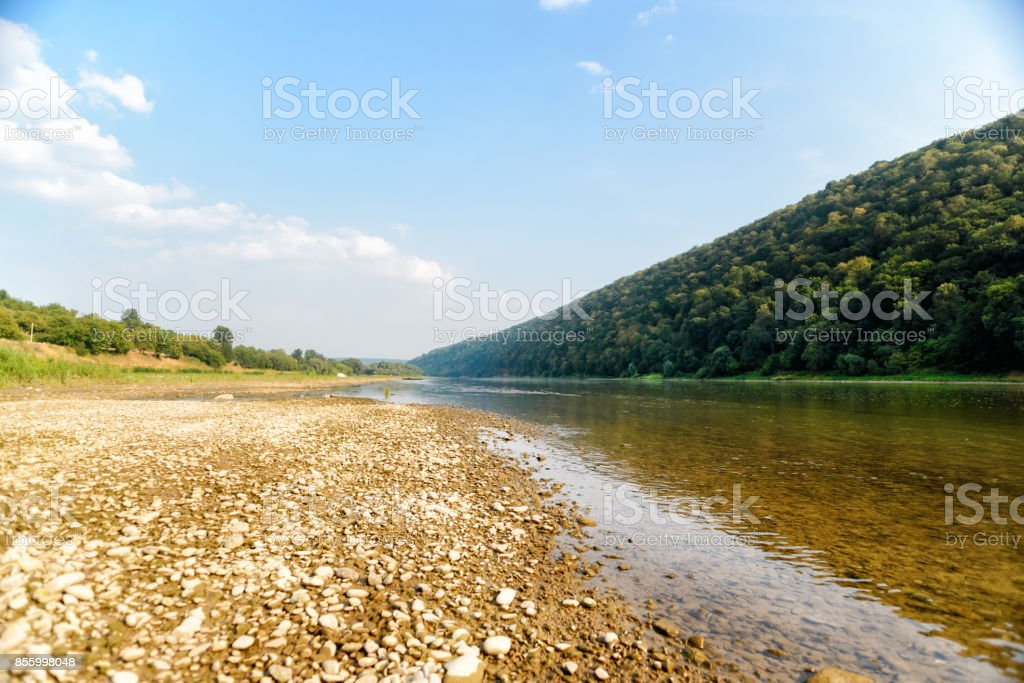A pile of stones on the bank of the Buller River, with the river in the background and the surrounding high cliffs covered in bush stock photo
