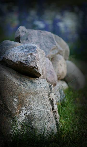 Gestapelte Steine mit Blumen im Hintergrund – Foto
