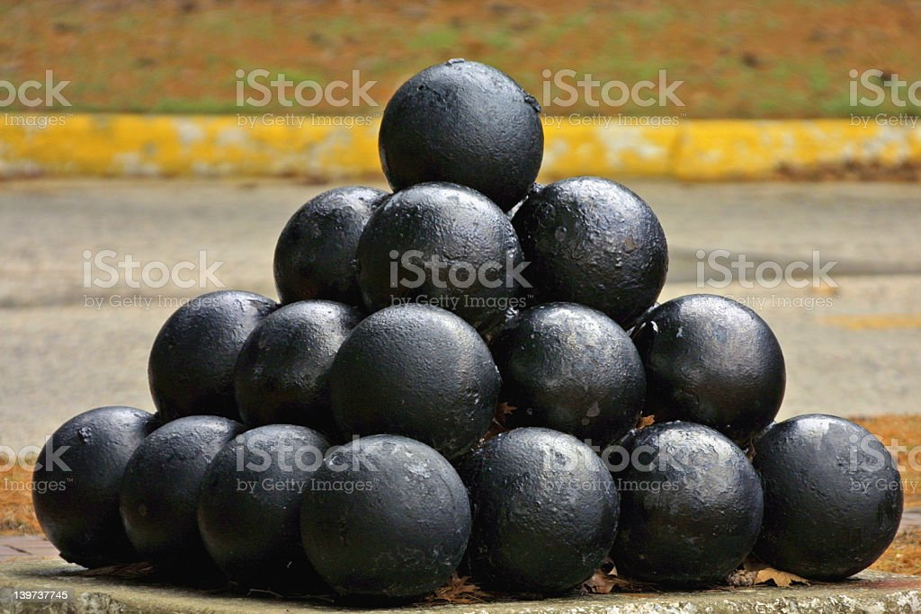 A pile of thirty cannonballs stacked on top of each other  stock photo
