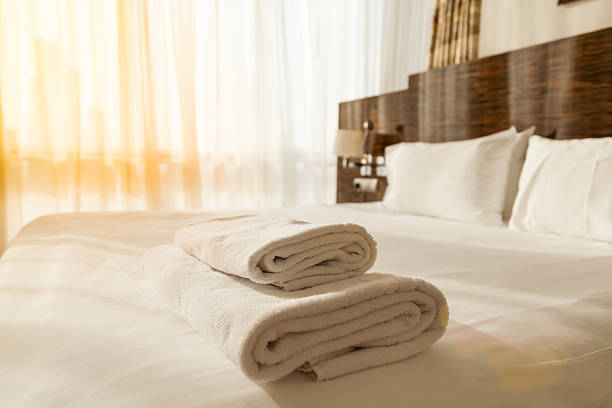 Pile of towels on the bed Stacked fresh white bath towels on the bed sheet. Close-up. Lens flair in sunlight inn stock pictures, royalty-free photos & images