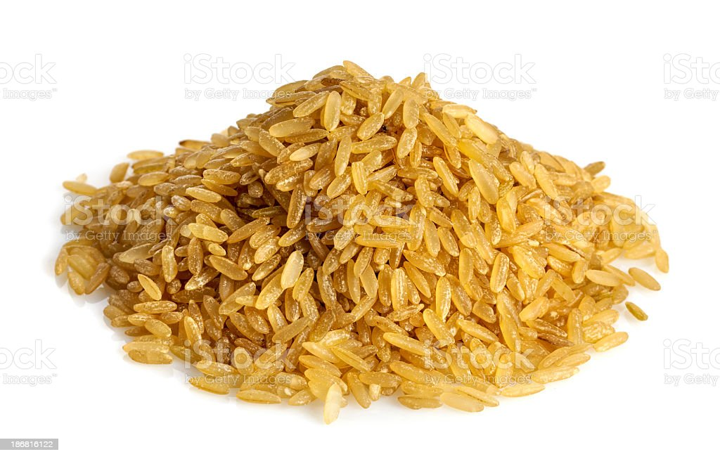 A pile of uncooked brown rice on a white background royalty-free stock photo