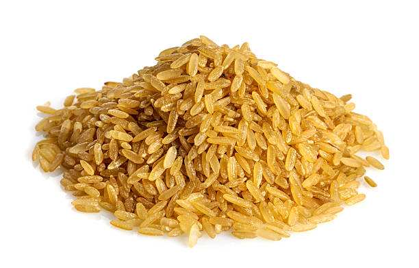 A pile of uncooked brown rice on a white background stock photo