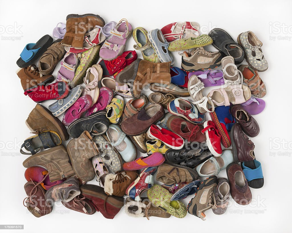Pile of used children shoes, white background stock photo