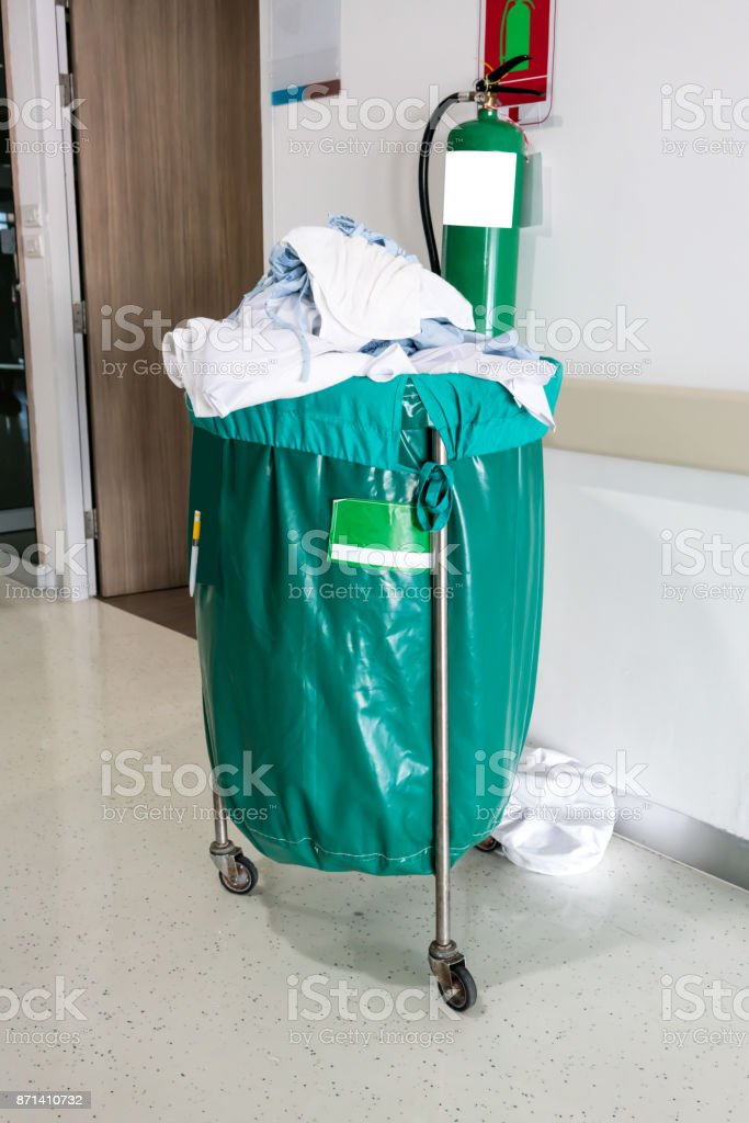 A pile of used clothes in hospital movable trolley with green bag for laundry. stock photo